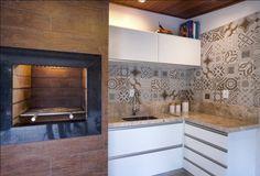 Varanda gourmet com 30m2, bancada em bege bahia. Revestimento da parede em marmore travertino romano bruto, e nicho com porcelanato que imit...