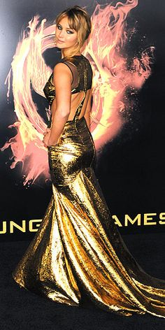 The Hunger Games's heroine flashes her fighting form in a back-baring, Prabal Gurung gold lamé fishtail gown accented with Jacob & Co. black diamond earrings at the movie's Los Angeles debut. Read more: http://www.people.com/people/package/gallery/0,,20576263_20578190,00.html#21133088