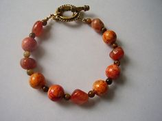 Orange beads reminiscent of Autumn leaves and Fall colors looks beautiful together with natural gemstone jasper beads as round spacers between the ceramic beads and gemstone nuggets within the bracele