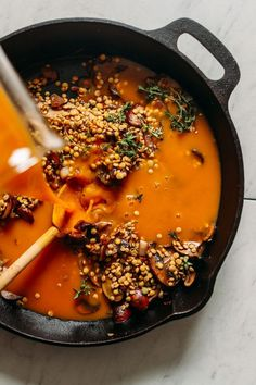 Pouring vegetable broth over lentils and veggies in a cast iron skillet to make gluten-free Lentil Mushroom Stew