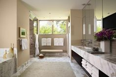 A thick marble countertop coordinates with the gorgeous marble floors and bathtub in this spacious bathroom. Neutral walls allow the marble the utmost attention, and crisp, clean lines create a contemporary feel.