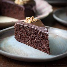 Eine Scheibe feuchter Schokoladen-Walnuss-Kuchen mit Schokoladen-Ganache und einer Walnuss-Hälfte serviert auf einem blauen Teller mit dem größeren Kuchen dahinter.