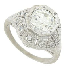 A dazzling 1.55 carat, EGL certified, I color, Si clarity round cut diamond rises above the face of this spectacular engagement ring. Abstract cutwork mountings drape down the sides and shoulders, each set with a fiery diamond. Intricate engraving and delicate milgrain decorate the ring. The antique style ring is fashioned of platinum and measures 13.80 mm in width. Size 6. We can re-size.