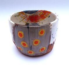 Simple form pot with 12 orange/yellow dotty stem leading to scratched through orange/tallow flower motif. 11cms high x 14cms wide © Linda Styles Ceramics 2014