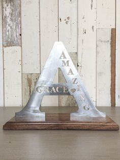 "$59.00   Beautiful handmade metalwork ""A"" with wood stand reading ""Amazing Grace""  11 inches tall  Customize your order with your own letter and your favorite scripture, quote, or your name.  Call the MBC shop at 214-821-1777 or email us through our contact page for details."