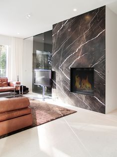 This beautiful fireplace is surrounded by the characterful marble Temporary Brown in BOOKMATCH motif. Design: Stijn ontwerpt - Photo: Studio52 #Haard #fireplace #interiordesign #Bookmatch #naturalstone #natuursteen #marmer #marble #potierstone