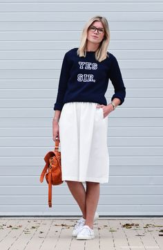 99e3724b9 Marry a navy print crew-neck sweater with a white pleated midi skirt for a  laid-back and fashionable look. Finishing with a pair of white leather low  top ...