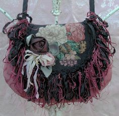 The Gypsy Rose Bag ~  A little bit romantic.  A little bit on the wild side. Youthful, yet wise with age.  The front flap is salvaged from an antique tapestry, dressed up with fringe created from several different trims giving it an eclectic look.  Hand made roses on a corsage with little charms dangle from the ribbons.  Body of the bag is made from a salvaged vintage damask upholstery in a deep dusty rose.  Inside completely lined with pocket.