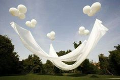 Floating canopy Baloons filled with helium, attached to fishing line, anchored with hooks or gold tees. The balloons support the fabric.