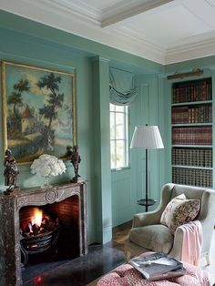 In this Northern California home by designer Suzanne Rheinstein, a landscape painting overlooks the library, whose walls are painted in Benjamin Moore's Stratton Blue. A 19th-century wing chair from Lucca is covered in a Lee Jofa corduroy.