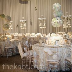 Low arrangements of ivory and soft-pink roses mixed with taller topiaries and floral chandeliers to give the tables depth.