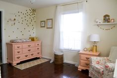 How great is this coral-painted vintage dresser?! We love the pop it provides next to the polka dot accent wall. #nursery #pinkandgold