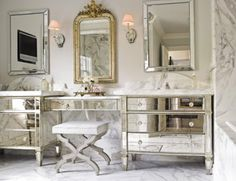 Master Bath of Mirrors and Marble  A vanity table links a pair of mirrored bureaus fitted with sinks. Thick slabs of honed Calacatta marble for backsplashes and counters, along with Waterworks Opus faucets and an antique gilt mirror, complete the dressy, old-world European feeling of this bathroom by Carrie Hayden.
