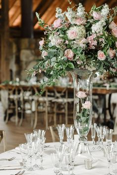 Tall glass vases, large floral centerpieces, indoor wedding reception decor, light pink roses // David Schwartz Photography