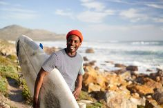 A young Black surfer carrying a surfboard and wearing a wetsuit explores a rocky coastline searching for good surf. Styled by: Bielle Bellingham Photographer: Micky Wiswedal Model: Mandla Ndlovu Young Black, Surfboard, Searching, Wetsuit, Surfing, The Unit, Stock Photos, Explore, Portrait
