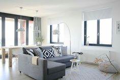 Sala com sofá cinza e paredes brancas com detalhes chamativos design escandinavo