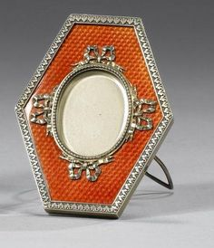 A Fabergé silver-gilt and enamel photograph frame, Moscow, before 1896, of vertical hexagonal form, the oval aperture with four ribbon bows, enamelled in translucent orange over basket-weave engine-turning, with engraved acanthus borders, scrolled easel support.