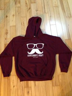 Maroon Hoodie.  Check out Gentlemen's Draft Clothing at https://www.facebook.com/GentlemensDraft   $2 from each item sold is donated to prostate cancer research.  Join us in  helping to fight cancer, one shirt at a time.   Stay classy like never before with our signature moustache and glasses logo on our custom designed threads.   Also check us out on: Instagram - gentlemens_draft