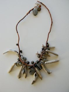 natural driftwood sticks are used as pendants in this earthy necklace. combined with beach pebbles, agate slices, jasper and pietersite beads, the wooden pieces make a striking and wonderful necklace. very personal and unique, everything is arrayed along a wrapped cord that gives this necklace a sculptural feel. the length is 23 inches (plus the 4 inch long central dangles)... the bleached driftwood is a wonderful pale color and the stone elements are a perfect compliment. lightweight and…