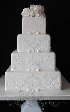 Elegant four tier wedding cake with royal iced stencilling and sugar roses