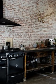 kitchen contrasts - bare brick and black - railway house by jeroen van zwetselaar