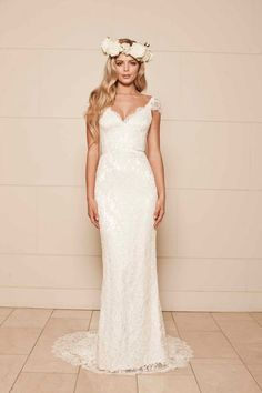 Ivory corded lace over ivory liquid silk. V neckline cross-over bodice with low V back. Hand appliquéd lace with scallop trim and capped lace sleeves.