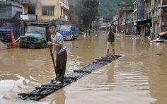 De 'carona' com um morador, jornalista filma o trajeto sobre uma jangada improvisada em rua alagada de Jianghua Yao, na província chinesa de Hunan. Ao menos uma pessoa morreu e 270 mil foram afetadas pelas fortes chuvas que atingem a região.