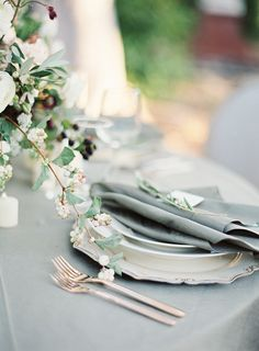 Soft grey linens, rose gold flatware, and white berries make an elegant tablescape.