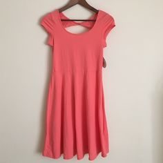 "SO cotton dress Med coral short sleeve a-line Super cute and comfortable cotton spandex  blend short sleeve dress features cap sleeves, a line feminine skirt, and a window pane open back with twist detail.  Dimensions 30"" bust, 26"" waist, 35"" length from shoulder to hem. SO Dresses Midi"