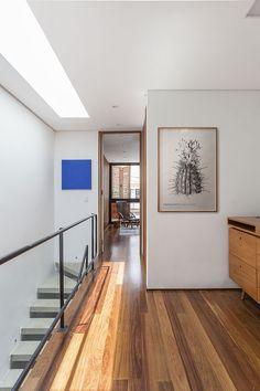 Decoração de casa geminada com luz natural. No corredor obra de arte.