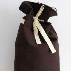 Plecak w kolorze czekoladowo-brązowo-fioletowym. Wewnętrzna worek plecaka obszyty jest płótnem surowym.Prosta wytrzymała konstrukcja. Wewnątrz znajduję się jedną kieszeń. Posiada 8 oczek przez które przeplatana jest wstążka bawełniana.     Wymiary:   Szerokość 35cm   Szerokość dna 8cm   Wysokość od ramiączek 41cm  Wysokość całkowita 55cm