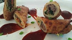 ECLECTIC SOUL ROLLS WITH A KOREAN BBQ SAUCE AND GARNISHED WITH SCALLIONS AND SESAME SEEDS
