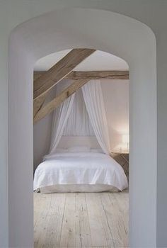 Simple attic bedroom that has wooden beams for a rustic accent.
