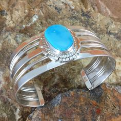 This beautiful Sterling Silver Bracelet with intricate silver work, features Kingman Turquoise found in Northwestern Arizona. Created by Navajo jewelers and Navajo silversmiths. Colors may vary due to