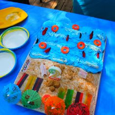 "Pool/Beach Party Cake-vanilla cake with chocolate cupcakes, topped with peach rings, swedish fish, fruit by the foot, and brown sugar with drink umbrellas. Signs read ""happy birthday"" and ""warning shark sighted keep out"" super easy and was a big hit at the party!"
