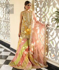 Amber shirt adorned with mainly light golden embellishment on neckline, hemline and side slits. Pink peach dupatta adorned with embellished border and stripes. Multiple color sharara adorned with border on hemline, stripes and motifs. Pakistani Mehndi Dress, Bridal Mehndi Dresses, Pakistani Wedding Outfits, Pakistani Wedding Dresses, Pakistani Dress Design, Bridal Outfits, Bridal Lehenga, Lehenga Choli, Pakistani Couture