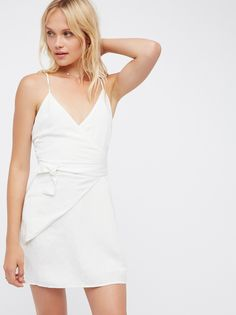 Turismo Wrap Dress | Easy linen mini dress featuring an effortless wrapped design in front with a tie detail. Adjustable crisscross straps. Lined.