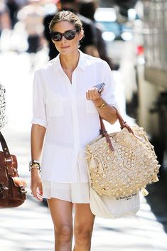Olivia Palermo wears a white button-up shirt, white pleated skirt, cream knit bag, sunglasses and stacked bracelets.