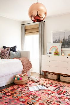 Children's room with a Tom Dixon copper pendant light, and a pink rug