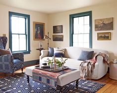 The home's remote location renders window treatments unnecessary. Mid-1800s homespun blankets cover the wing chair, ottoman, and hardwood floor.