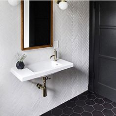 Floor to ceiling herringbone tiles with a narrow sink make for a stylish small powder room.