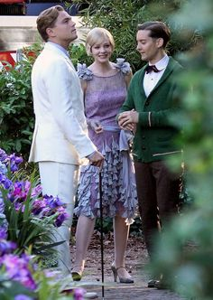 """Leonardo DiCaprio (Jay Gatsby), Carey Mulligan (Daisy Buchanan) and Tobey Maguire (Nick Carraway) on set of """"Gatsby"""".  Full view of lavender lace dress with dropped waist, cornflower blue tassel details and handkerchief hemline."""