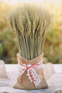 Wheat in burlap sack as rustic wedding decor. Event Design: Fairy Godmother --- http://www.weddingchicks.com/2014/06/04/country-burlap-and-lace-wedding/