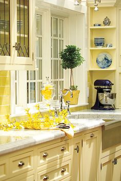 Kitchen with creamy yellow cabinets and marble counters -- Architecture by Olson Lewis Dioli & Doktor Architects