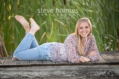 Blonde teen wearing jeans and a patterned blouse lays on a dock and poses for senior portrait. Photo by Steve Holmes Photography Unique Senior Pictures, Photography Senior Pictures, Lake Photography, Senior Photos Girls, Fashion Photography Poses, Senior Girls, Girl Pictures, People Photography, Teen Girl Poses