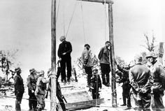 Suspected Russian partisans just hanged by the Germans. Undated, undisclosed location. The Germans by the gallows are busy securing the ropes as the victim wearing black moves his hands in a last, desperate gesture. On the right foreground, two Germans are involved in conversation; the death of three men is not really important -- business as usual.