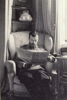 'Nicholas II, Emperor of Russia (1868-1918)' (1902) Unknown Person (photographer). Photograph of Nicholas II, Emperor of Russia reading the St Petersburg News in the Mauve Boudoir at the Alexander Palace, Tsarskoye Selo. He is sitting in an armchair looking down at a folded newspaper. There is a window behind him to the right and a lamp with a lace cover above him.