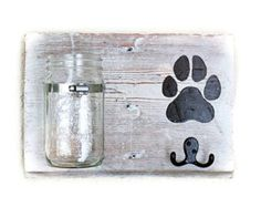 Perfect for the dog lover in your life! This rustic, personalized dog treat & leash holder features a wide mouth Mason jar for treats and a double prong hook to hold your dogs collar or leash. The jar is mounted on an authentic reclaimed barn wood board which has been given a distressed finish in antique white (pictured). This item comes ready to hang. Color options: 1) Distressed white board with black lettering 2) Walnut stained board with cream colored lettering Please include your…