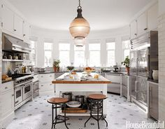 """Designer Joan Schindler made a """"pass-through"""" refrigerator the Connecticut kitchen's quiet star. The Nero Marquino marble countertops and twin 19th-century light fixtures are also understatedly electric. The massive custom center island is on casters, but mostly to enhance the visual effect — it's really too heavy to move.    - HouseBeautiful.com"""