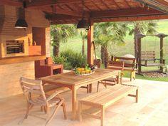 Com o intuito de promover o convívio familiar, a paisagista Paula Magaldi desenhou uma área gourmet em tijolos aparentes, seguindo a linha rústica das construções da Fazenda Bela Vista, em Itatiba, estado de São Paulo, Brasil. No entorno, há plantas tropicais como as palmeiras fênix (Phoenix roebelenii).  Fotografia: Divulgação.  http://mulher.uol.com.br/casa-e-decoracao/album/2015/11/03/jardim-de-fazenda-tem-fontes-bromelias-e-cantos-para-relaxar.htm#fotoNav=20